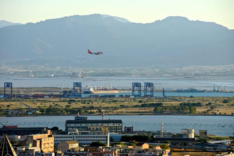 Panorama van Cagliari met een landend vliegtuig stock foto