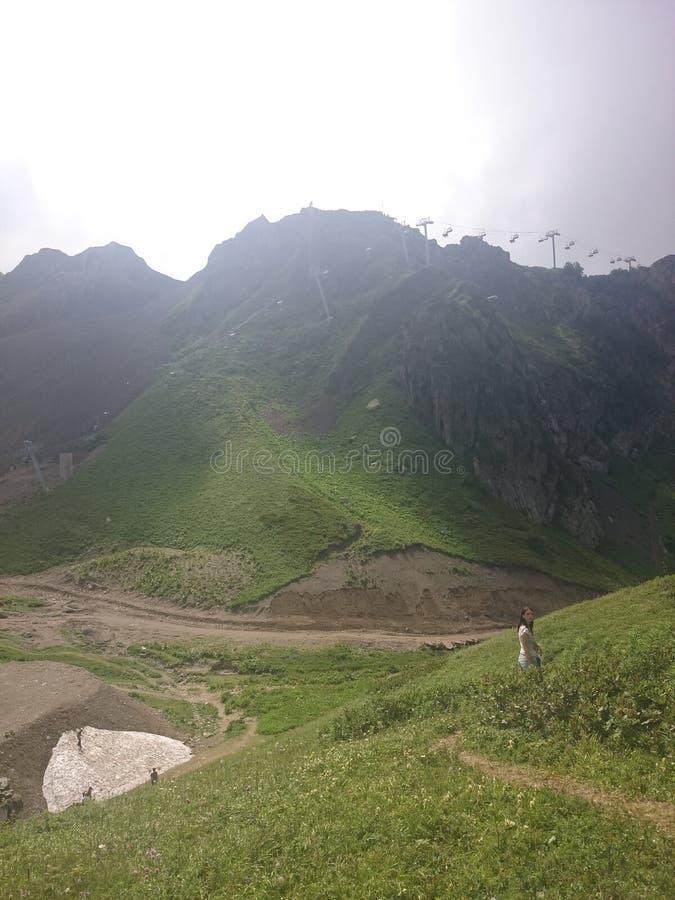 Panorama van de bergen en van de Aibga-rand met lage wolken Blijft van sneeuw en vers groen gras op de bergen dichtbij stock fotografie