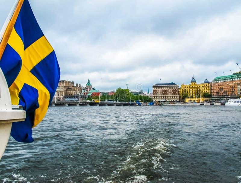 Panorama van de excursieboot met de vlag van Zweden op de mooie gebouwen van Stromkajen in het centrum van Stockholm royalty-vrije stock afbeeldingen