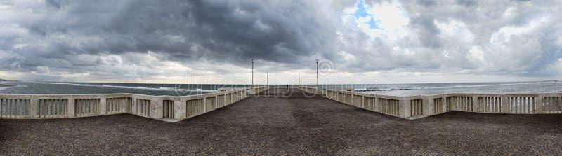 Panorama van de pier aan ruwe overzees met toneeldiehemel door wolken klaar voor de regen bij afstand een mens wordt behandeld di royalty-vrije stock foto's