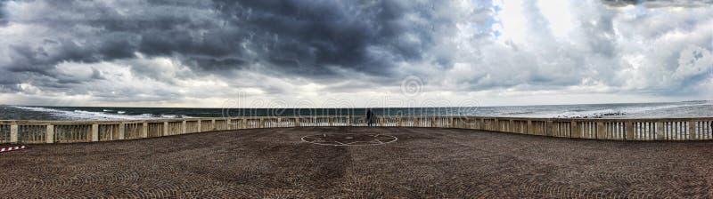 Panorama van de pier aan ruwe overzees met toneeldiehemel door wolken klaar voor de regen bij afstand een mens wordt behandeld di royalty-vrije stock foto