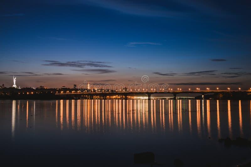 Panorama van de stad van Kiev bij nacht De horizon van de Kyiv linkeroever met Paton-brug over Dnieper-rivier stock foto