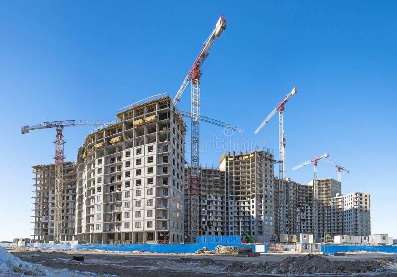 Panorama van een bouwwerf met hoge kranen van flatgebouwen in microdistricts stock afbeeldingen