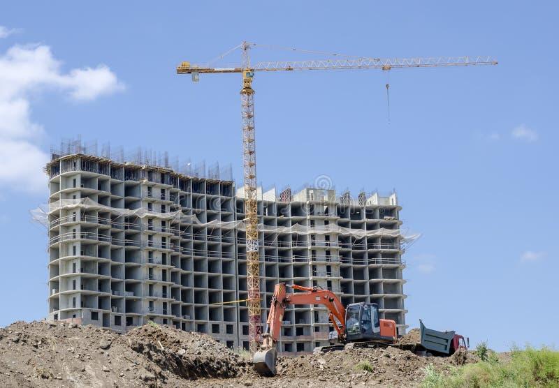 Panorama van een bouwwerf met een kraan, een huis in aanbouw, een graafwerktuig en een stortplaatsvrachtwagen royalty-vrije stock afbeelding