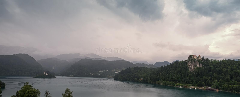 Panorama van een grijze en vreselijke ochtend in de Alpiene bergen op Afgetapt Meer stock foto