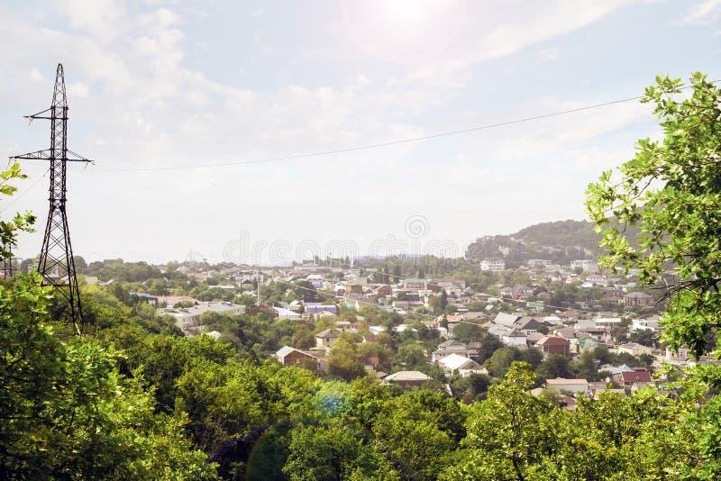 Panorama van een kleine stad en een elektrische toren met hoog voltage om elektriciteit aan de bevolking te leveren stock afbeeldingen