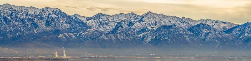 Panorama van een opvallende berg tegen bewolkte hemel torenhoog over een wazige vallei stock afbeeldingen