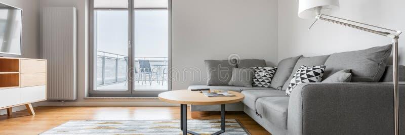 Panorama van grijze en witte woonkamer stock afbeeldingen