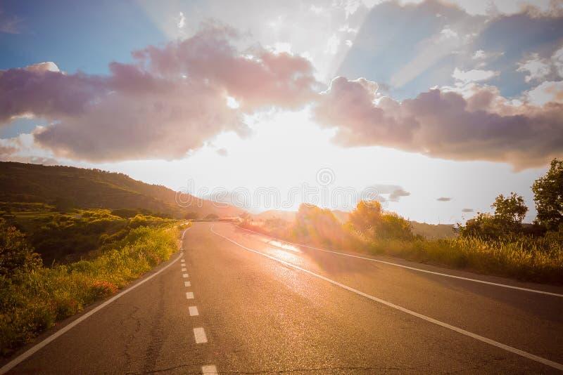 Panorama van lege asfaltweg onder zonsonderganghemel, schemer lichte zonnestraal stock foto