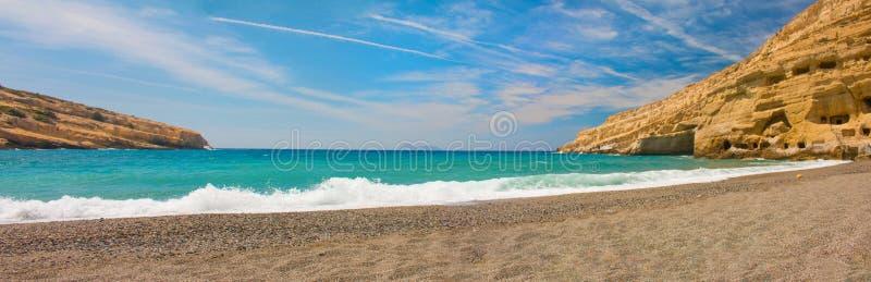Panorama van Matala, mooi strand op het eiland, de golven en de rotsen van Kreta stock foto's
