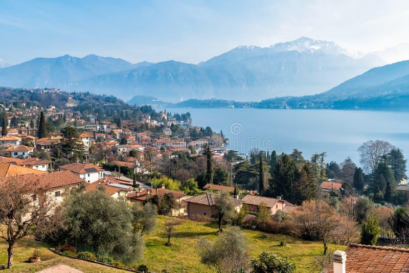 Panorama van Meer Como en Tremezzo-dorp met een lichte nevel op de achtergrond, Italië stock afbeeldingen