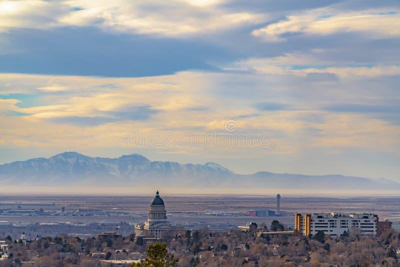 Panorama van Salt Lake City van de binnenstad tegen majestueuze berg en bewolkte hemel stock foto
