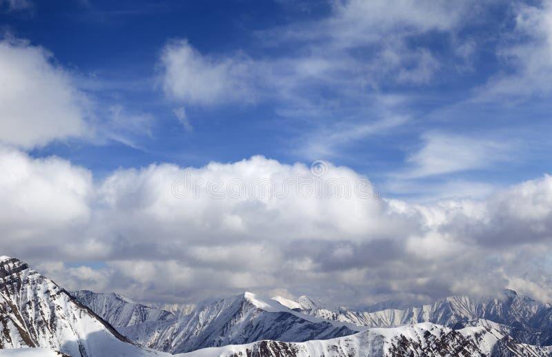 Panorama van sneeuwbergen en blauwe hemel met zonovergoten wolken royalty-vrije stock afbeelding