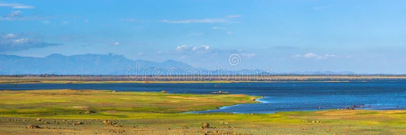 Panorama van Uda Walawe-reservoir met bergen op de horizon stock afbeeldingen