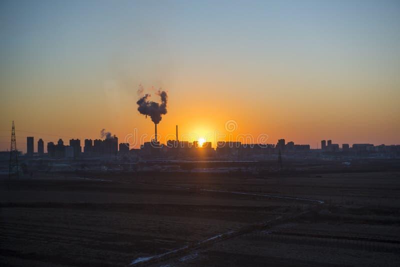 Panorama van zonsondergang in de stad met silhouet van gebouwen en industriële fabriek, verontreinigingsstad of stadsconcept stock afbeelding