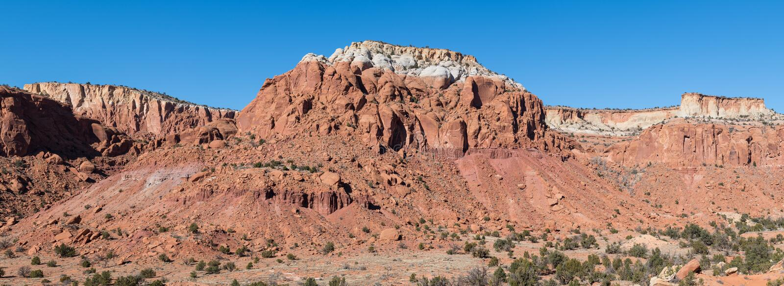 Panorama of a landscape of colorful red rock mesas and cliffs in the American Southwest. Panoramic view of a vast landscape of red rock mesas and cliffs in the royalty free stock photography