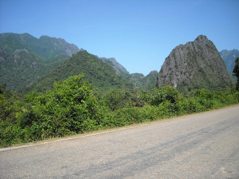 Panorama of verdant hills in South-East Asia. Road through the mountains around Vang Vieng, Laos. Hiking through rugged foreign mountains and hills, amid royalty free stock photos