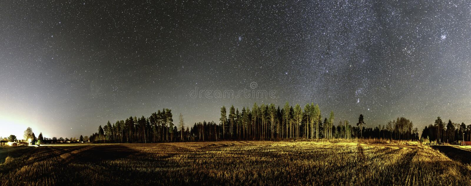 Panorama of very clear deep starry skies with Milky Way above harvested field and wild Scandinavian pine forest, autumn time. Near Umea, Vasterbotten, Northern royalty free stock images