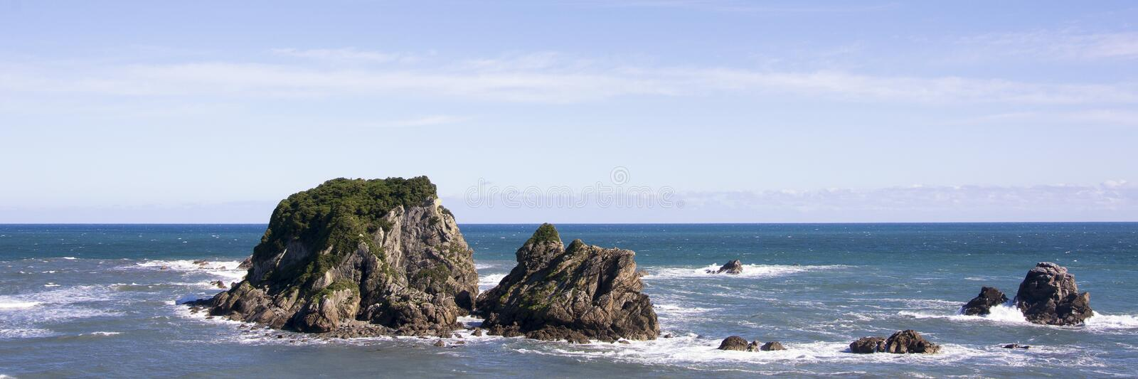 Panorama view on the beautiful New Zealand west coastal area, with the Tasman Sea, rocks, blue water and a clear sky. This is a rough, untamed and sparsely royalty free stock photo