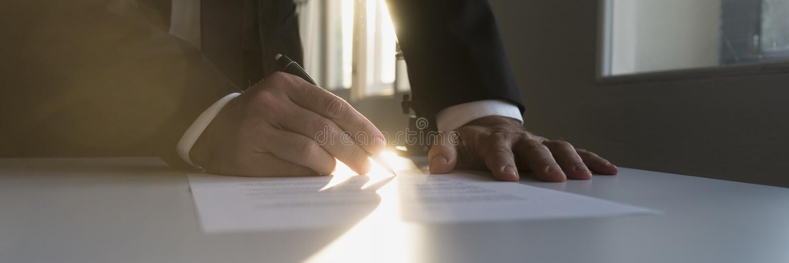 Panorama view of businessman in a shadowy office signing contract stock images