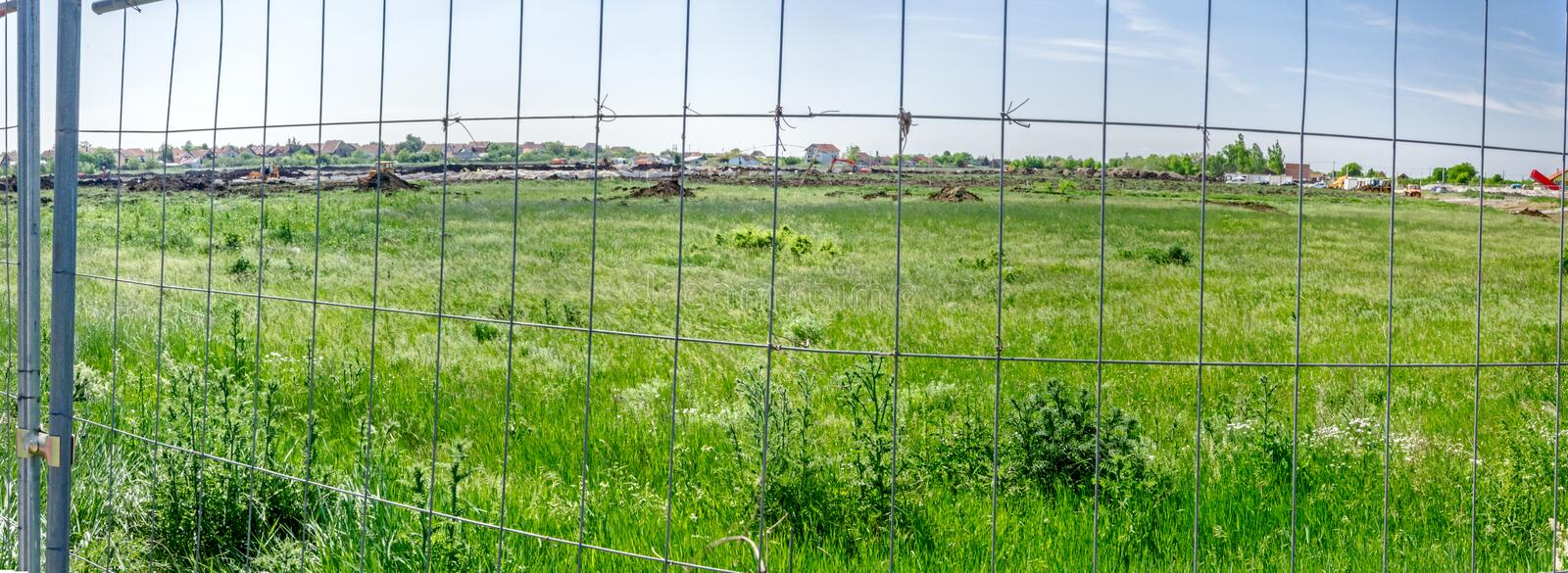 Panorama view on the construction site through a fence wire. Wide panorama of a building site. Landscape transform into urban area with machinery, people are stock images