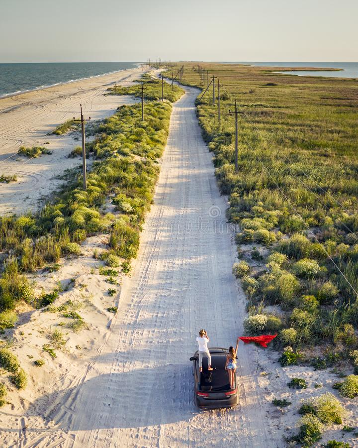 Panorama view, extreme couple travelers on car at country beach road among sea, sand, nature. Summer adventure, drone. Panorama view, extreme couple men women stock photo