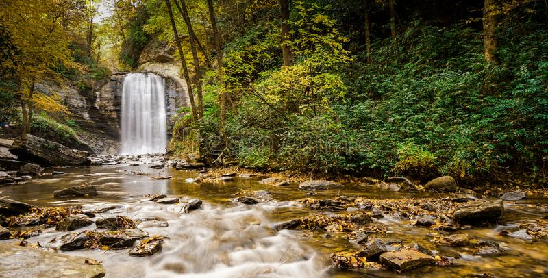 Looking Glass falls in the Appalachians of North Carolina in late autumn with fall color foliage. Panorama view of Looking Glass falls in the Appalachians of royalty free stock photography