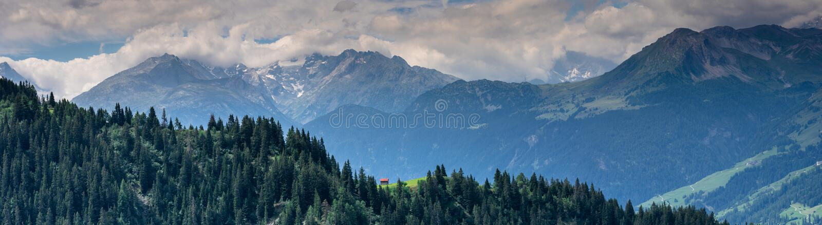Panorama view of mountains and valley in Switzerland with red cabin royalty free stock image