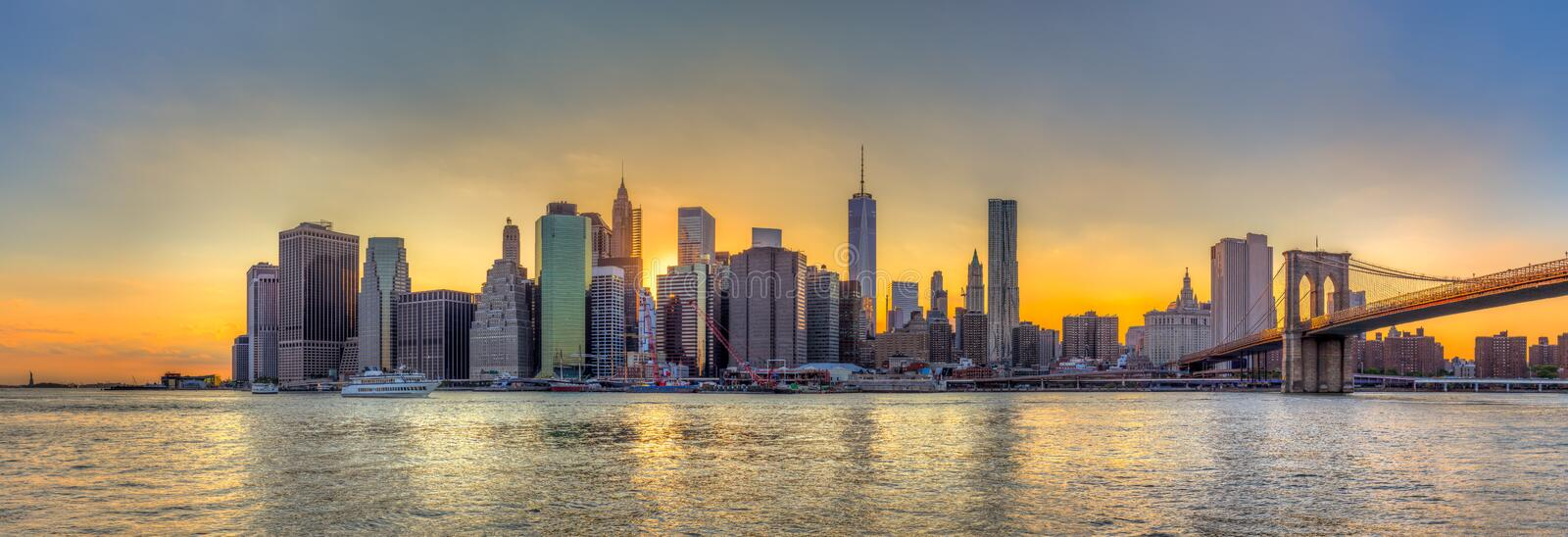 Panorama view of New York City downtown skyline and Brooklyn bridge at sunset royalty free stock images