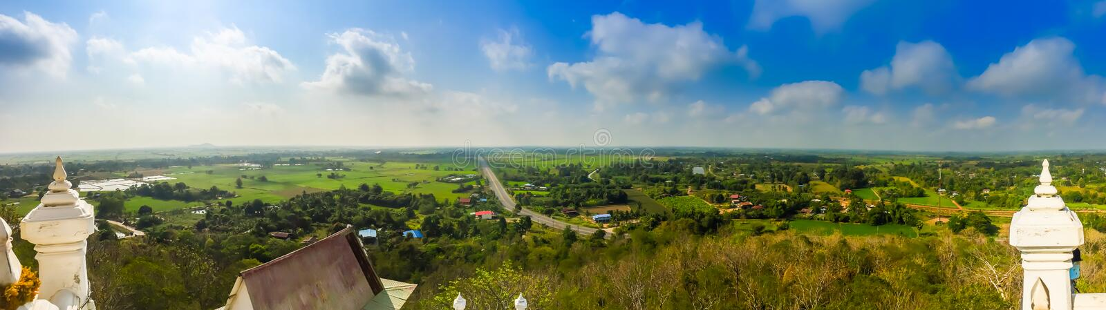 Panorama view over highway from hilltop around with countryside green rice fields and blue sky background. The provincial highway royalty free stock photography