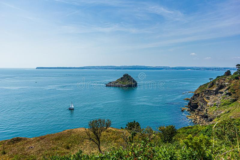 A panorama view of a rocky island surrounded by beautiful flat blue sea water with rocky coastline under a majestic blue sky and s stock photography