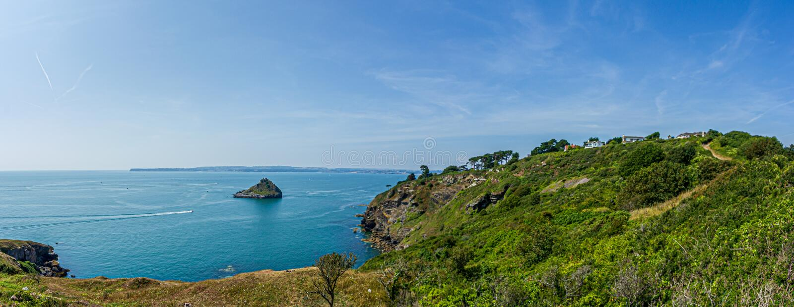A panorama view of a rocky island surrounded by beautiful flat blue sea water with rocky coastline under a majestic blue sky and s. Ome white clouds stock image