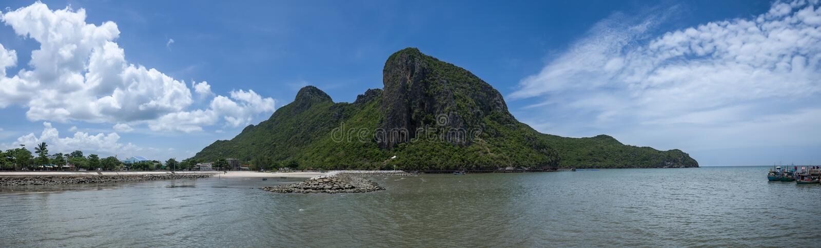 Panorama view of the sea and rock beach with long big mountain and beautiful blue sky, cloud in background. Prachuapkhirikhan Thailand royalty free stock photos