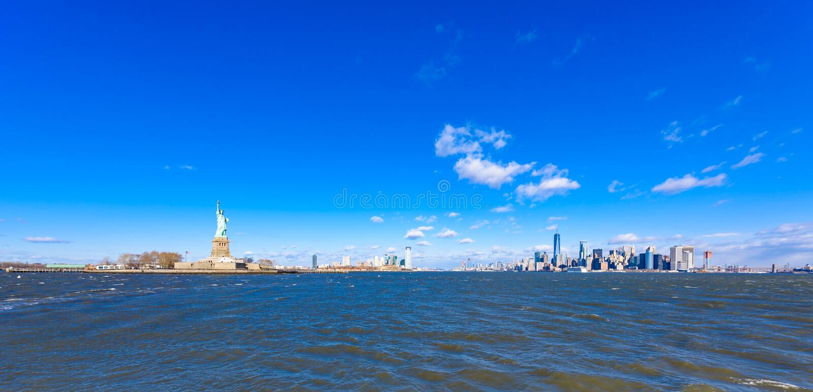 Panorama View of Statue of Liberty at New York City with Manhattan Skyline over Hudson River - USA royalty free stock photo