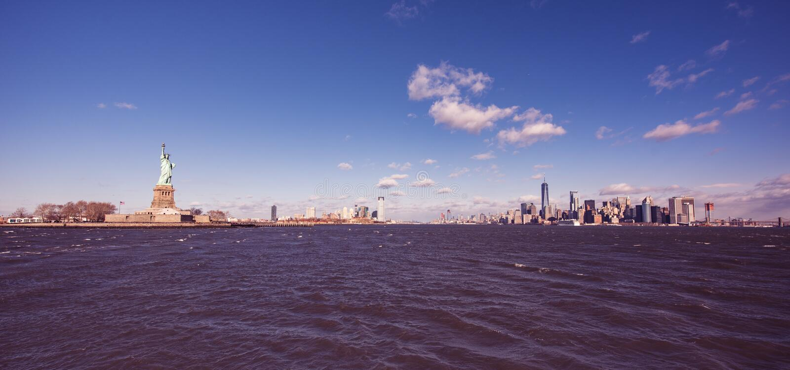 Panorama View of Statue of Liberty at New York City with Manhattan Skyline over Hudson River - USA royalty free stock images