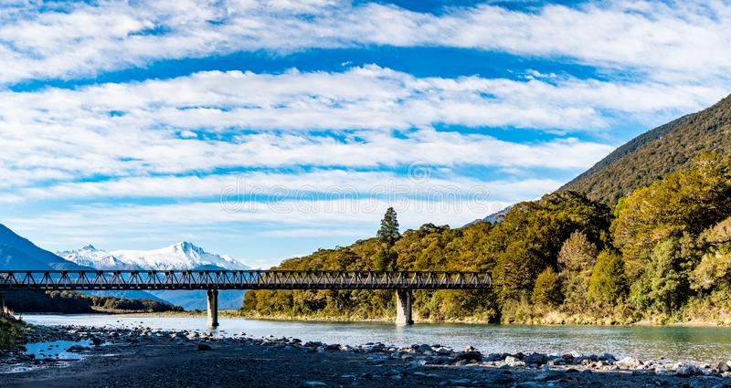 Panorama view, a Stunning landscape of the snow mountain and a bridge across the river. Blue sky and some cloudy. I stock photos