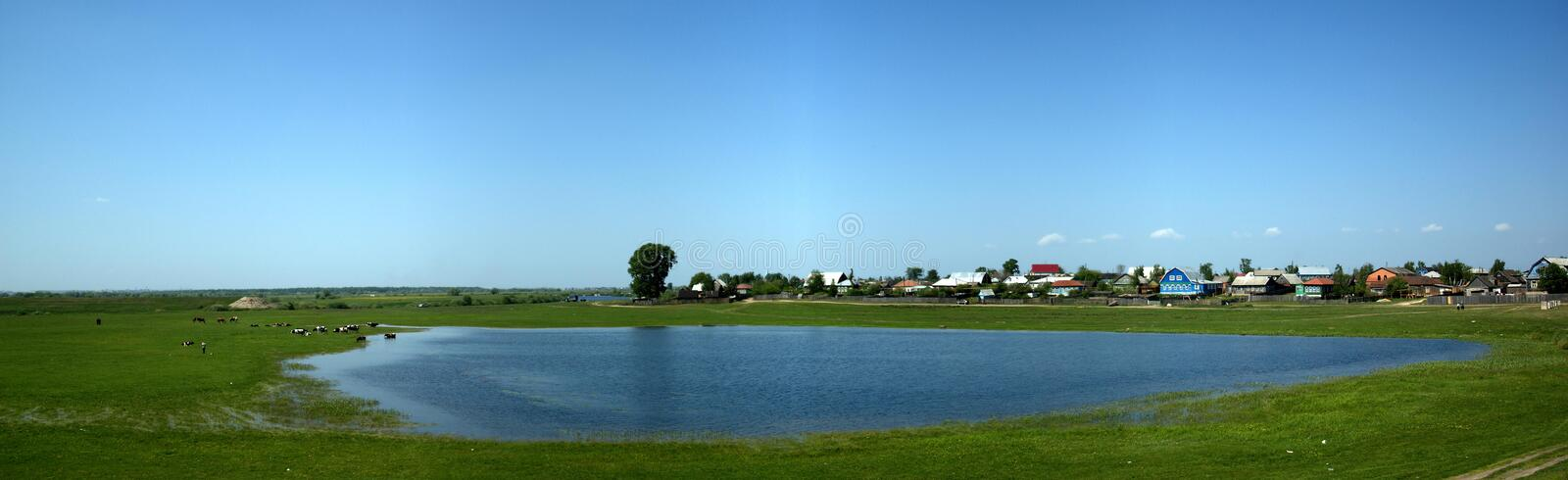 Panorama in village with blue lake and green grass