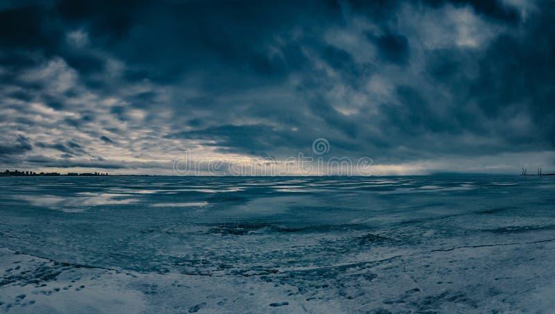 Panorama- vinterlandskap med dramatisk himmel och djupfryst vatten arkivbilder