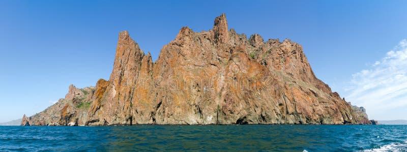 Panorama von Felsengebirgsmassiv des vulkanischen Ursprung auf Seeufer lizenzfreies stockbild