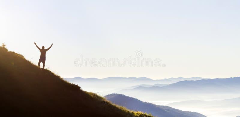 Panorama von offenen Armen des jungen erfolgreichen Mannwanderer-Schattenbildes auf Bergspitze stockfoto