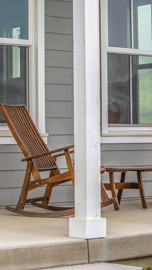 Panorama Voorportiek van een huis met bruine schommelstoelen en rechthoekige witte pijlers stock afbeelding
