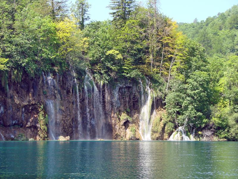 Fantastic panorama and natural scenery of forests, mountain rivers and waterfalls near Plitvice Lakes in Croatia. Panorama of waterfalls flowing into the lake royalty free stock images