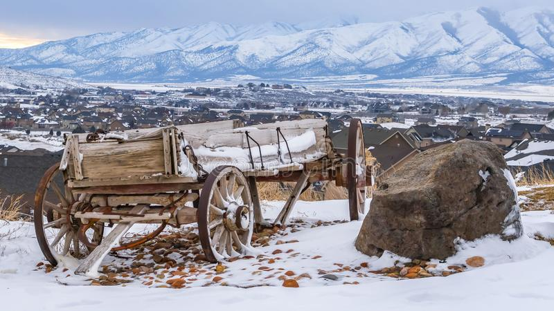 Panorama Weathered wooden cart and huge rocks on top of a hill with snow in winter royalty free stock images