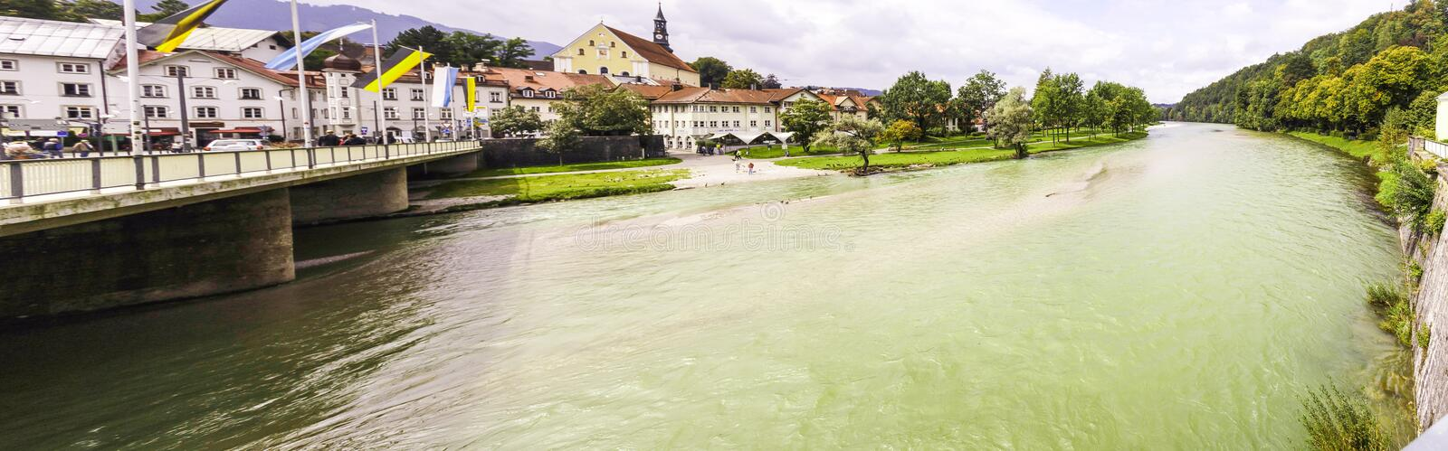 Panorama of a wide river flowing under a bridge. Panorama of a wide green river flowing under a bridge as it passes through a town from the lush green stock photography