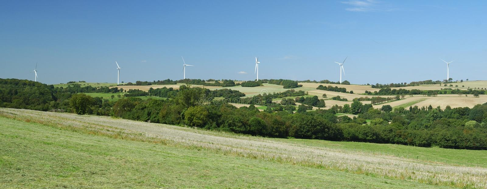 Panorama of windfarm over a hill. In France royalty free stock image