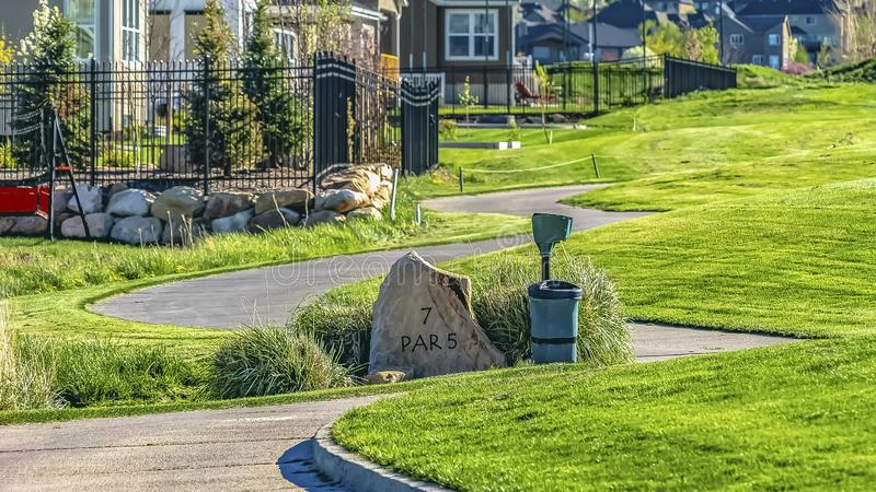 Panorama Winding pathway on a grassy terrain in front of houses viewed on a sunny day. The base of a towering mountain can be seen in the distance stock image