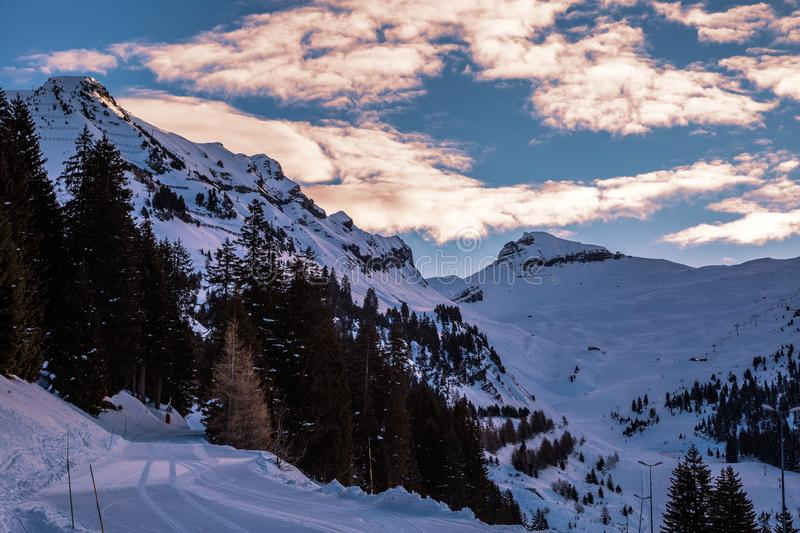 Panorama of winter snowy Alps. Colored sky at sunset sunset in snowy mountains. Flaine, Grand Massif, France royalty free stock images
