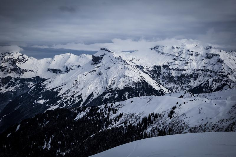 Panorama of winter snowy Alps. Panorama with dramatic sky, Alps in Flaine area, Grand Massif, France royalty free stock image