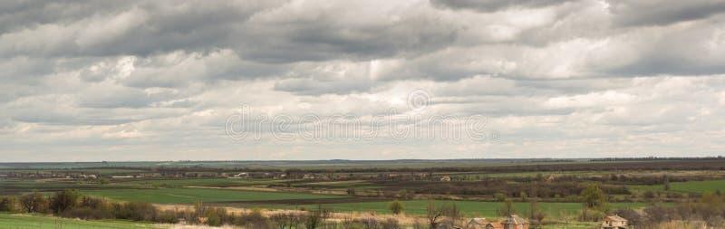panorama Wiosna Wiejski krajobraz z popielatymi chmurami nad wioską i polami fotografia royalty free