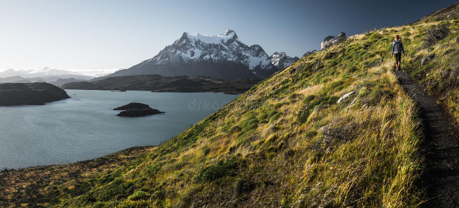 Panorama with the woman hiker walking. On the trail in the Torres del Paine National Park. Chile stock photography